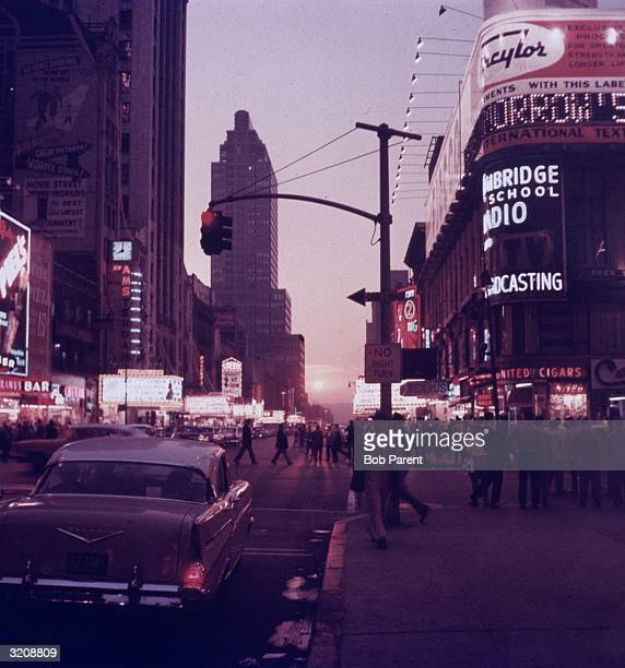 Street scene of Times Square with neon movie theater marquees and people crossing the street New York City