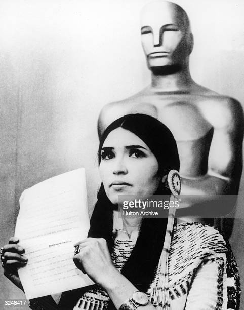 Sacheen Littlefeather holds a written statement from actor Marlon Brando refusing his Best Actor Oscar on stage at the Academy Awards Los Angeles...