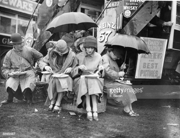 A group of racegoers having lunch in the rain on Derby day at Epsom