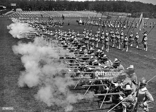 Soldiers in costume firing muskets during a rehearsal for the Aldershot military tattoo