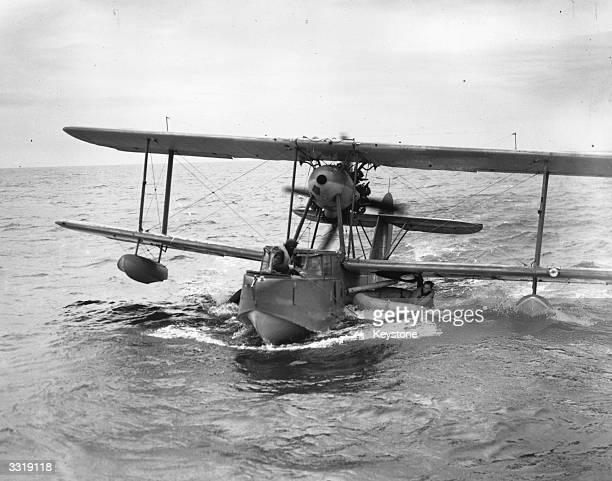 A downed pilot in his rubber dinghy hangs on to a Walrus amphibian flying boat as he waits to be picked up during a seaair rescue training exercise