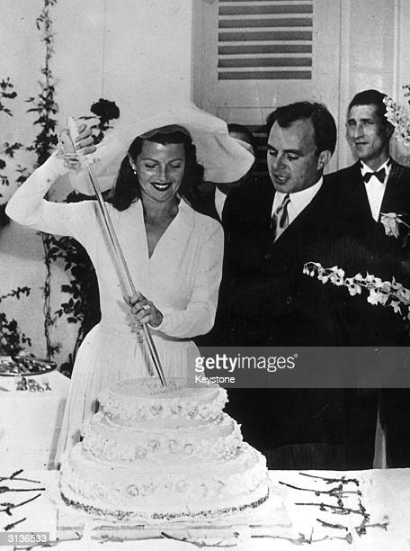 American actress Rita Hayworth with her husband the Prince Aly Khan cutting the cake on their wedding day