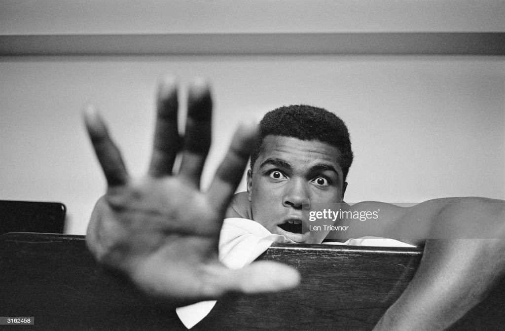 American Heavyweight boxer Cassius Clay (later <a gi-track='captionPersonalityLinkClicked' href=/galleries/search?phrase=Muhammad+Ali+-+Boxer+-+Born+1942&family=editorial&specificpeople=93853 ng-click='$event.stopPropagation()'>Muhammad Ali</a>) lying on his hotel bed in London. He holds up five fingers in a prediction of how many rounds it will take him to knock out British boxer Henry Cooper.