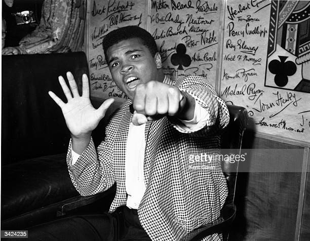 Supremely confident American boxer Cassius Clay holds up five fingers in a prediction of how many rounds it will take him to knock out British boxer...