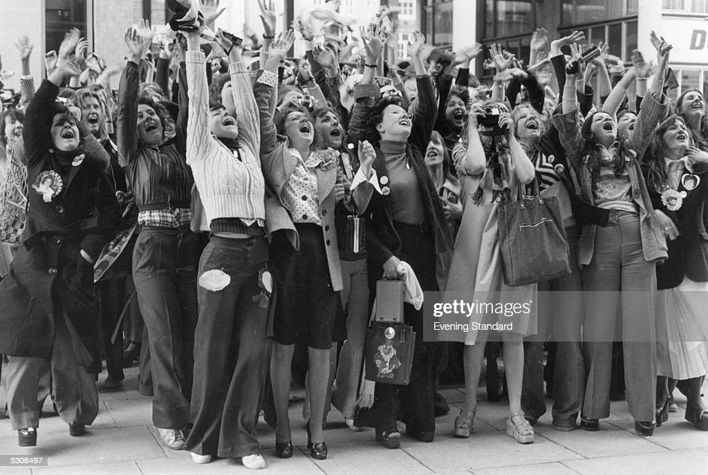 Fans of The Osmonds, some of whom have waited all night, cheer the group as they arrive at Capital Radio's offices in London.