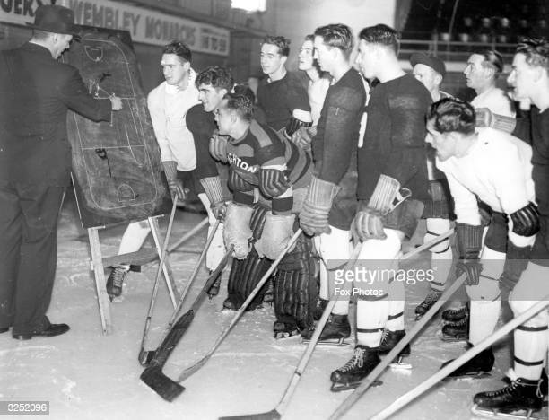 Ice hockey team the Brighton Tigers are given a lecture on team tactics by trainer Don Penniston