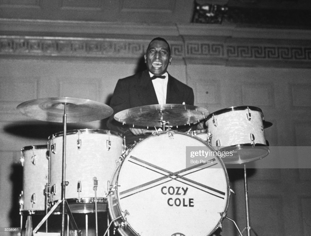 Musician Cozy Cole (1909 - 1981) plays drums while performing on stage with Louis Armstrong (not pictured) at Symphony Hall, Boston.