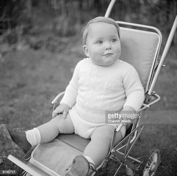A bonny baby in a jumper with buttoned shoulder fastenings