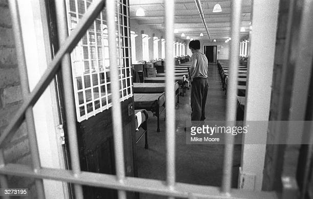 A young boy sweeping the floor in the dormitory at a Junior Detention centre in Send Surrey