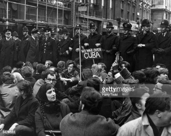 A crowd of CND demonstrators sitting in the road on Whitehall London in protest over the Cuban missile crisis A line of policemen are preventing the...