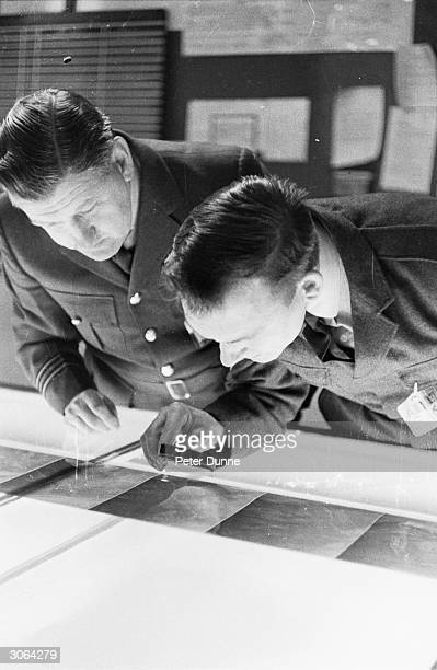 Two RAF men studying a map after the discovery of the body of moors murder victim Lesley Anne Downey on the Pennines