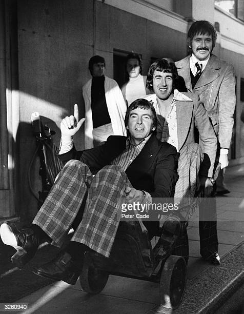 The vocal folk group the Bachelors Conleth Cluskey Declan Cluskey and John Stokes outside the Savoy Hotel in London playing with a fruit barrow