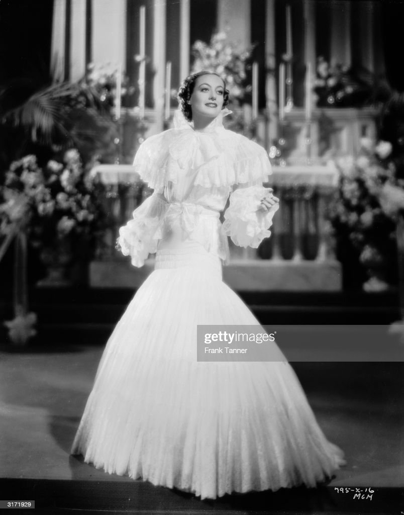 Joan Crawford models a white lace gown for her role as Mary Clay in the romantic comedy 'Forsaking All Others' directed by W S Van Dyke Costumes by...
