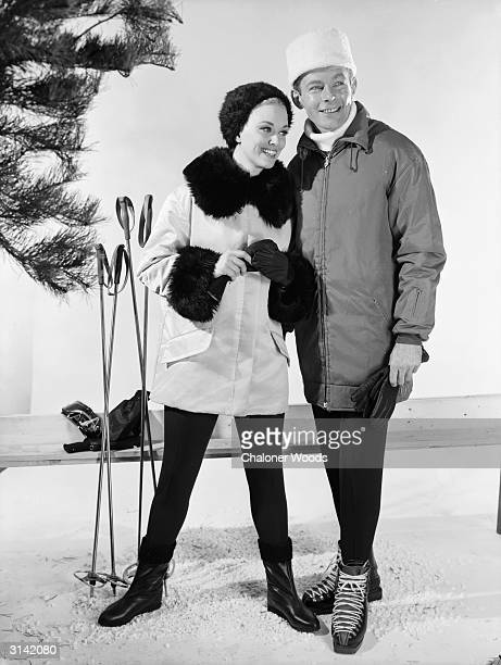 A couple modelling winter coats hats and gloves