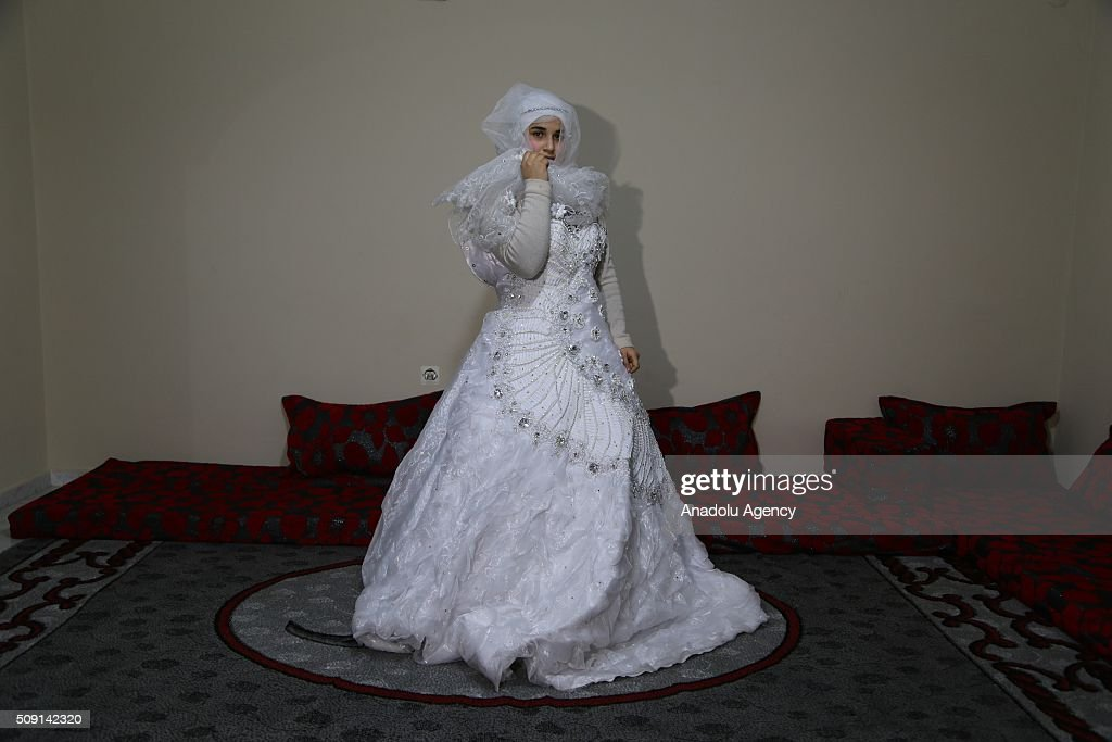 27-years-old Syrian refugee Hatija Ahdiy (C), fled from Syria due to ongoing civil-war, poses with her wedding dress at a house in Turkey's Syrian border city Hatay's Reyhanli District on February 08, 2016. Hatija had been making marriage plan but canceled due to Assad Regime's attacks. urkey spent US$ 8 Billion and hosts approximately 2 million refugees.