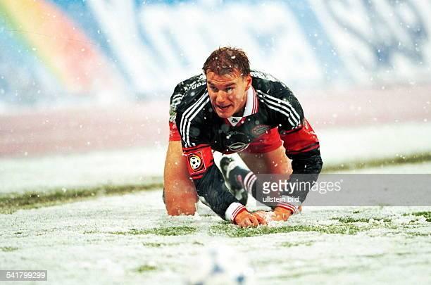 Sportler Fussball D kniet auf dem schneebedeckten Rasenwährend eines Spiels