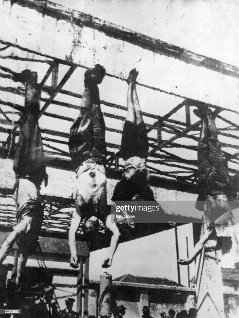 From the ramp of a big gasoline station, four bodies hang head downwards. Former Fascist dictator Benito Mussolini (1883 - 1945) and his mistress Clara Petacci are in the centre. The man on the right is Alessandro Pavolini, and the man on the left is identified by different sources as either Gelormini or Achille Starace.