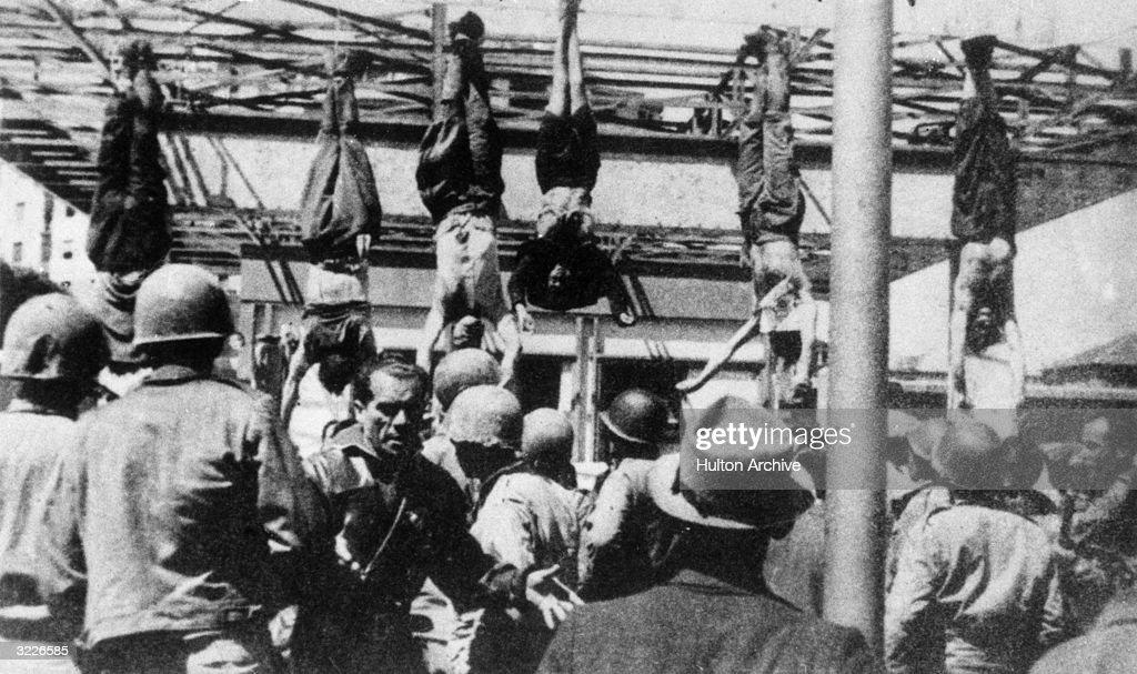 Italian fascist leader Benito Mussolini (1883 - 1945) and others captured with him, including his mistress, Clara Petacci, hang by their feet from a filling station after their execution at Giulino di Mezzegra, near Lake Como, Italy.