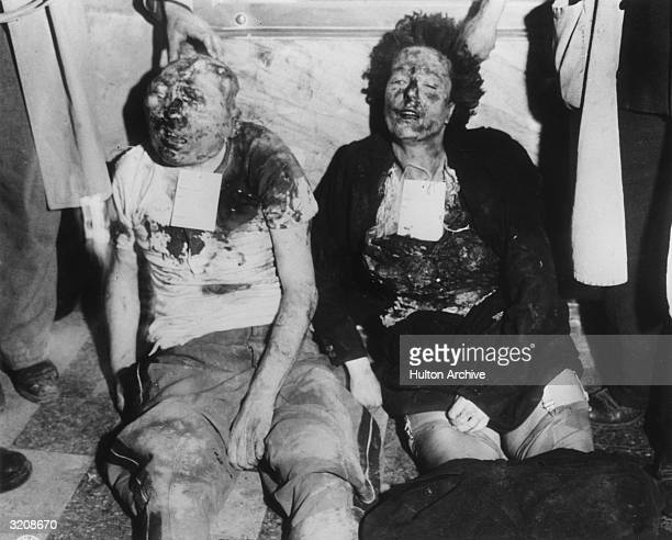 View of the mutilated bodies of Benito Mussolini and his mistress Clara Petacci propped up against a marble wall in Milan Italy World War II The...