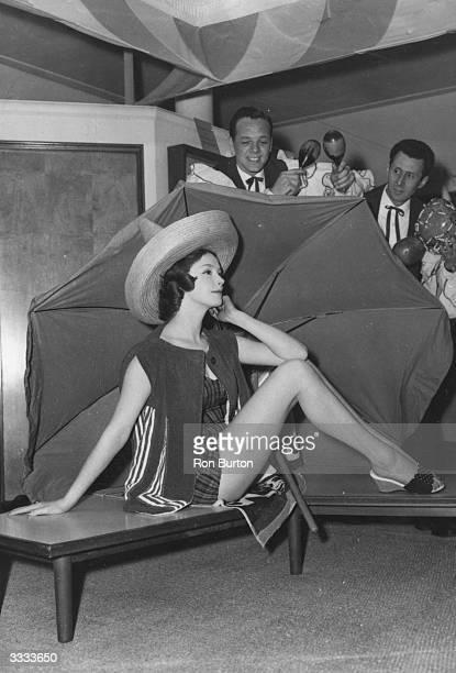 Margaret Brown models a tartan nylon swimsuit worn under a towelling jacket