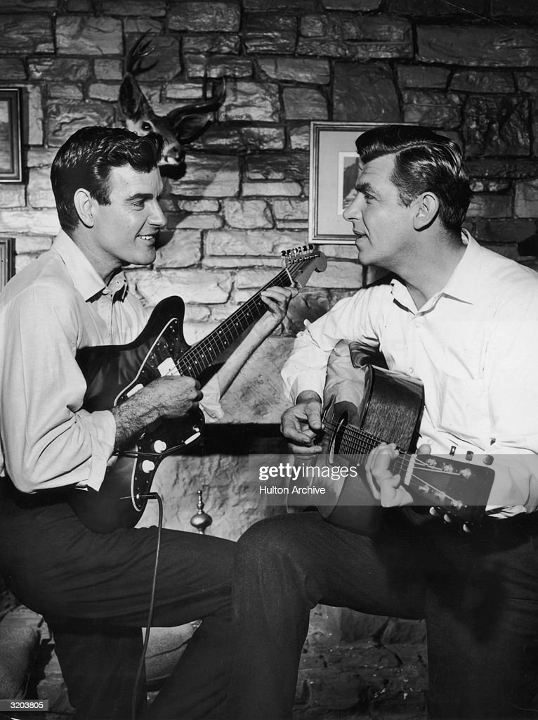 American actors James Best and Andy Griffith play a guitar duet while sitting in a living room in a publicity still from the television series, 'The Andy Griffith Show'. Best plays an electric guitar, as Griffith accompanies him on the acoustic guitar.
