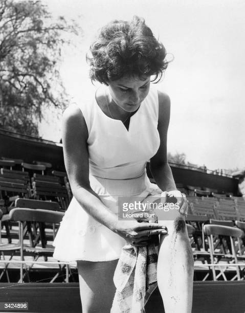 Miss M Schacht of Australia inspects her injured knee after beating Winnie Shaw in the quarterfinal of the women's singles at the London Hard Court...