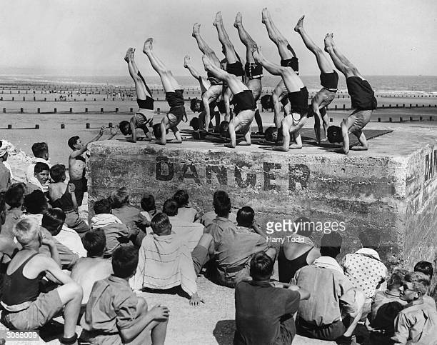 A group of boys from Dr Barnardo's Homes holidaying at St Mary's Bay Holiday Camp New Romney Kent give a gymnastic display on a sea wall