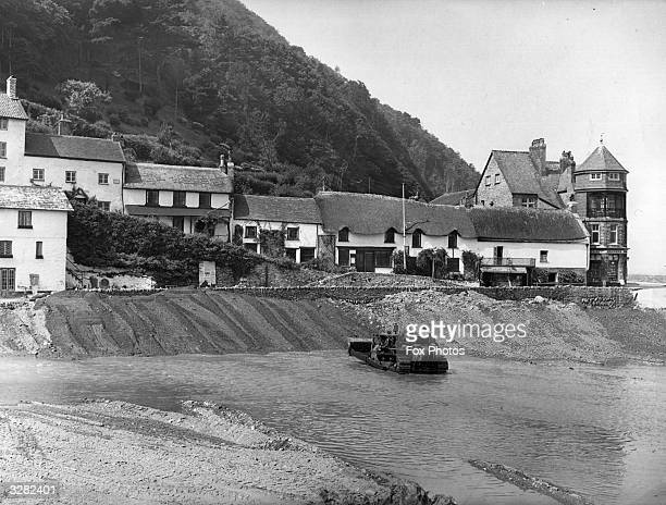 A bulldozer shoring up the main street of Lynmouth following flooding