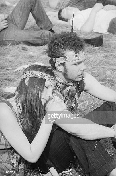 A hippy couple sitting on the grass at a Festival of Flower Children held in Woburn Park seat of the Duke of Bedford
