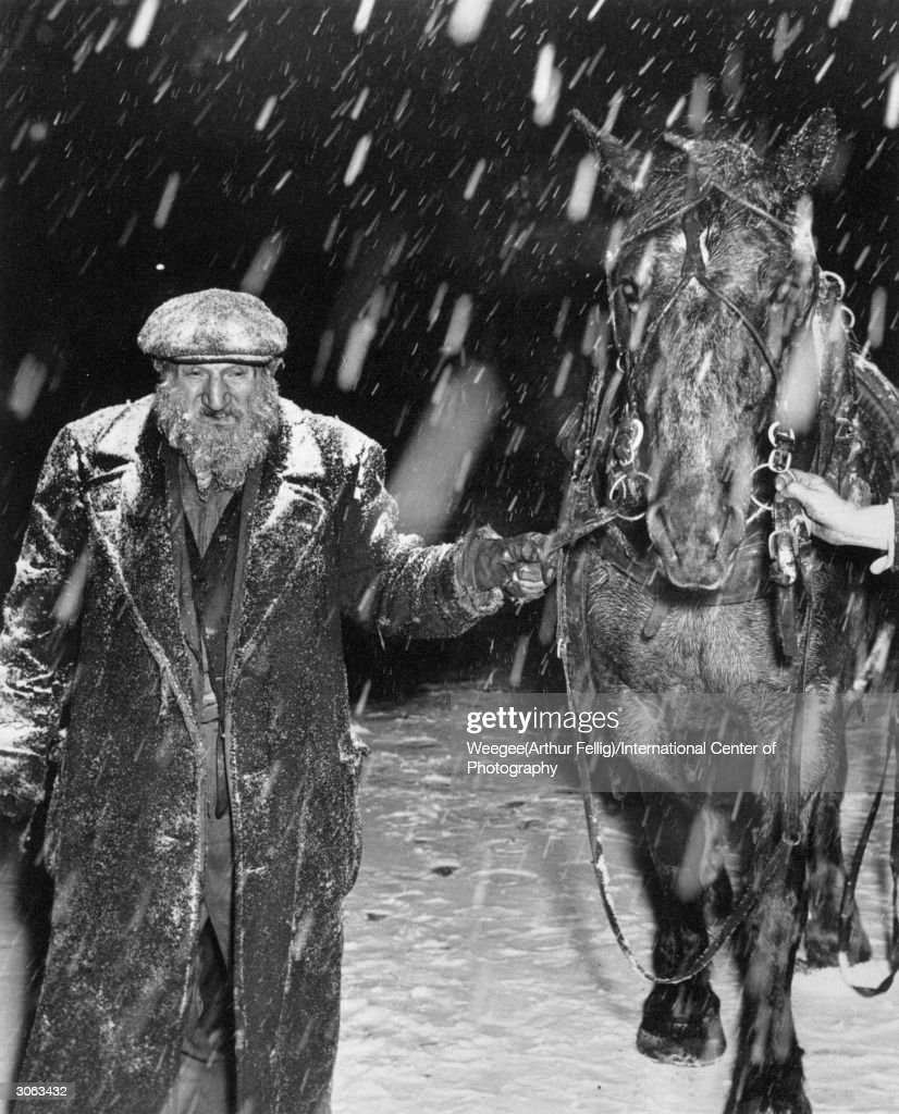An incident in the snowstorm. Rag peddler Sam Karshnowitz leads a horse along the street in a bitter snowstorm. The horse has been rented for the day to pull his wagon. (Photo by Weegee(Arthur Fellig)/International Center of Photography/Getty Images)