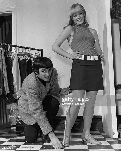 Footballer George Best takes a measurement for a mini skirt in his boutique