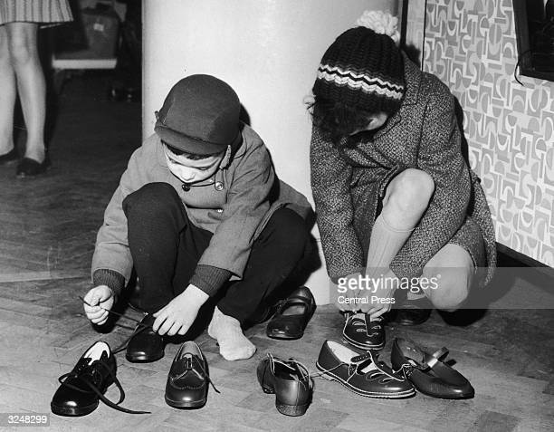 Michael Hobson aged six and his tenyearold sister Ann try on shoes at the Selfridges winter sale in London