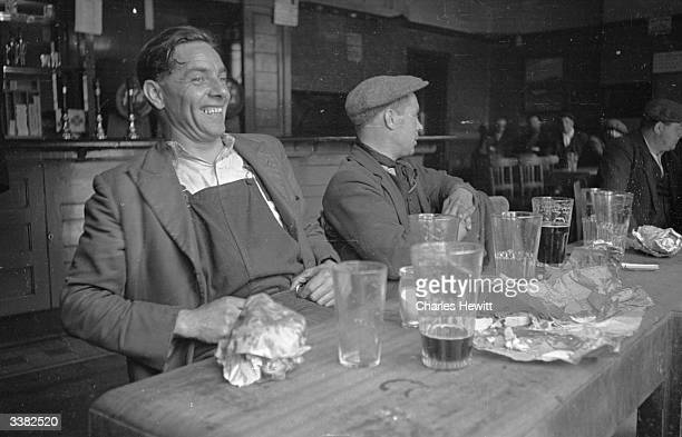 London dockers and members of the National Amalgamated Stevedores and Dockers Union relax in a pub near the Port of London's King George V Dock...