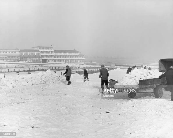 Teams of men clear the snow from Cheltenham racecourse before the venue reopens on March 12th The work has to be done by hand since machines would...