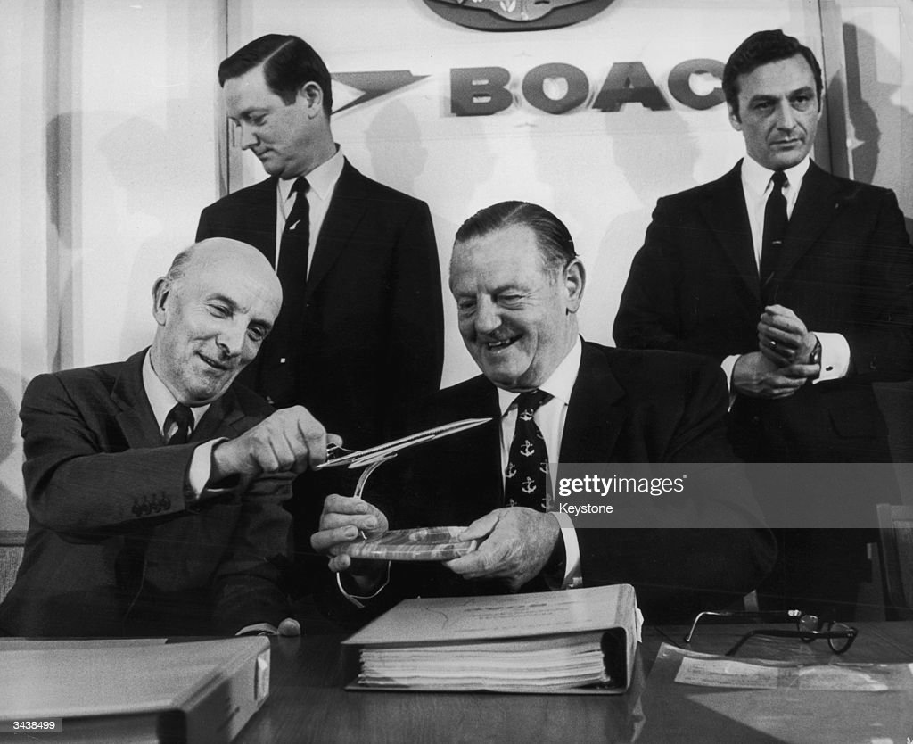 Aircraft engineer and industrialist Sir George Edwards (1908 - 2003, left) presents BOAC chairman Keith Granville with a silver model of a Concorde airliner after BOAC signed a contract to buy five of the aircraft.