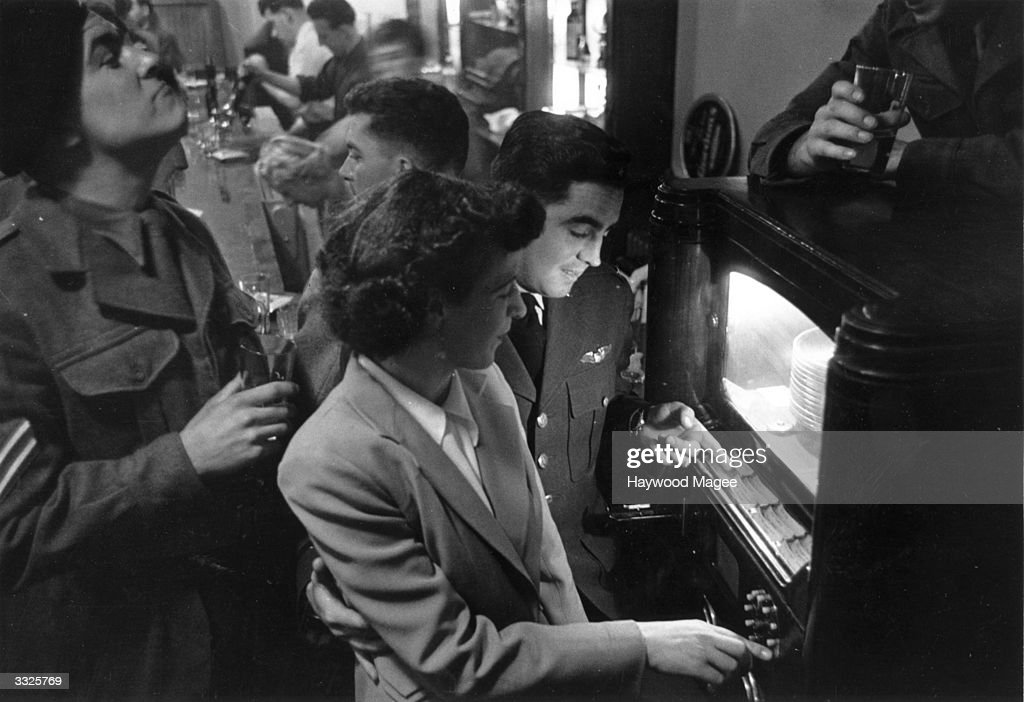 Members of the US Airforce stationed in Britain, selecting records to play on a juke box. Original Publication: Picture Post - 5927 - The Yanks In England - pub. 1952