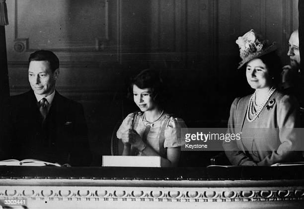 King George VI and Queen Elizabeth watching a performance from a box with Princess Elizabeth at the Coliseum Theatre London