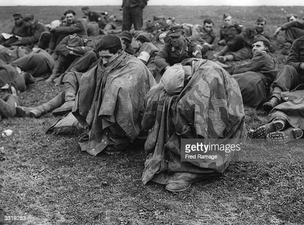 Tired and disconsolate German prisoners of war crouch under waterproof capes after their capture on the banks of the Rhine