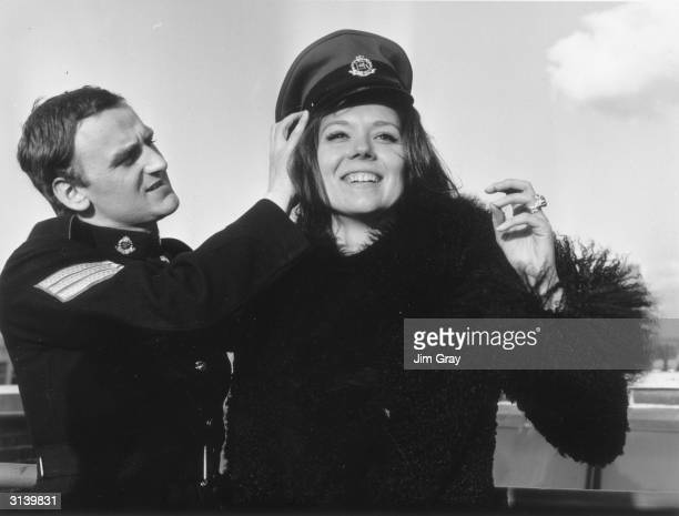 English actress Diana Rigg trying John Thaw's hat on in Hanover Square London Thaw's new series 'Redcap' is replacing 'The Avengers' in which Diana...
