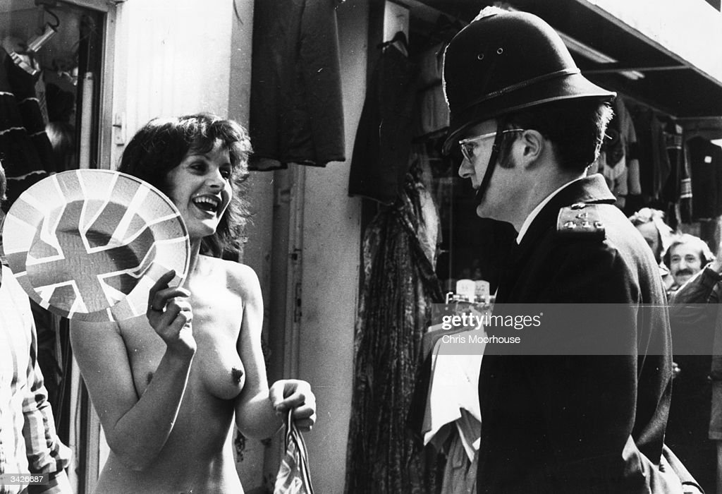A policeman advising Anne Bruzac, a model who is wearing no clothes in London's Carnaby Street, to get dressed.