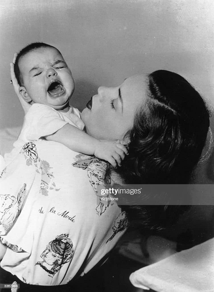 American actress Judy Garland holding her and film director Vincente Minnelii's daughter Liza who later became famous in her own right as an actress...