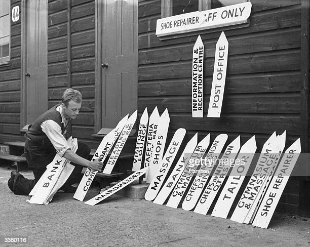 One of the workmen with some of the direction signs to be put up at the Olympic Centre in Richmond Park Surrey The 'village' will be home to 1400...