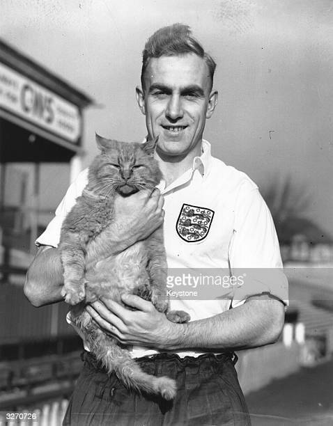 England captain Billy Wright holds Tiddles the cat who strolled onto the ground at Brighton during an England training session