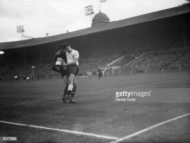 Yugoslav keeper V Beara helps England's Johnny Haynes off the field at Wembley after an injury in the EnglandYugoslavia international