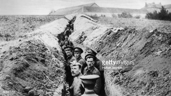 British soldiers lined up in a narrow trench during World War I
