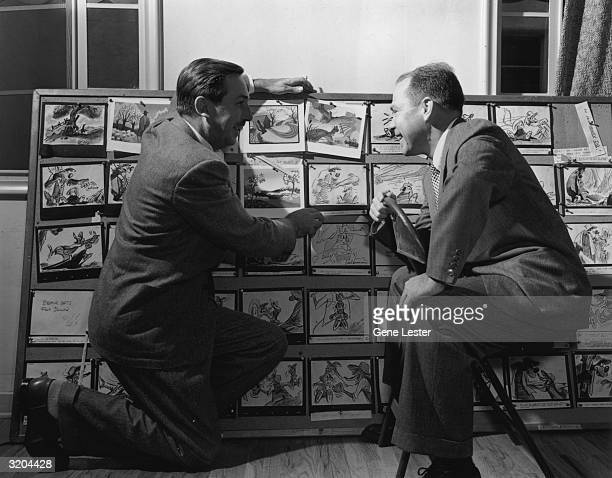 EXCLUSIVE American animator and producer Walt Disney kneels with American songwriter Johnny Mercer in front of cartoon storyboard sketches posted on...