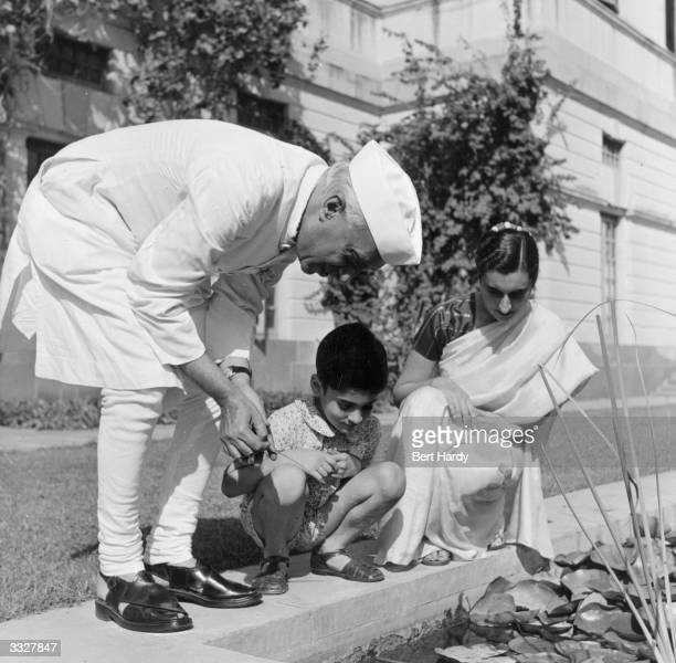 Indian Prime Minister Pandit Jawaharlal Nehru by a lily pond in the garden of his New Delhi home WIth him are his daughter Indira Gandhi and her son...