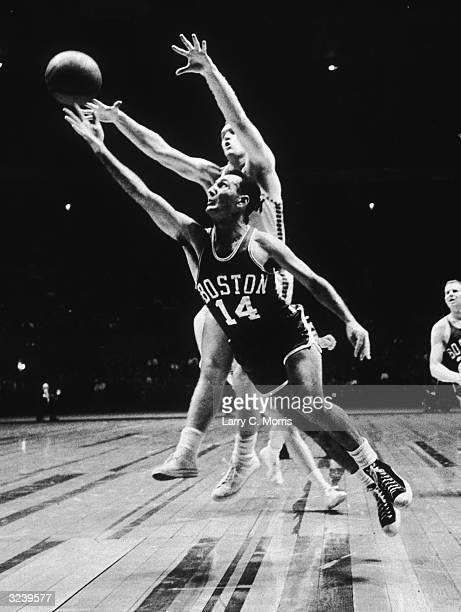 Basketball player Bob Cousy of the Celtics drives around Bob NcNeill of the Knicks to try an underhand layup in the Boston Celtics versus New York...
