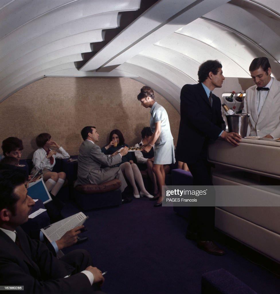 28Th Paris Air Show In Le Bourget 1969. Au Salon du Bourget 1969, dans le bar fumoir des premières classes sur Boeing 747, un stewart debout derrière le bar discutant avec un client et une hôtesse servant des petits fours aux passagers assis.