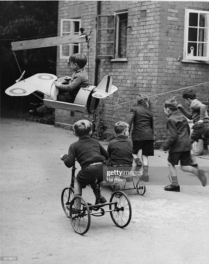 A young boy enjoys a ride in a model aeroplane, which runs on an overhead wire for 100 yards across the playground at Catherine's Home, Hampstead Garden Suburb.
